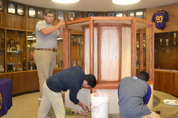 NEW TROPHY CASE -- Mr. Bright's students staining our new trophy case Nick Santos (left), Kyle Lackey (middle),