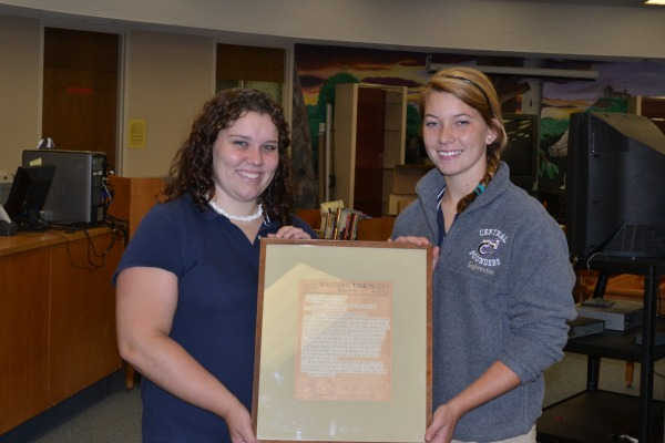 FIFTY YEARS LATER --Hali Smith (left) and Brittany Sylvester (right) show the official telegram sent by President John F. Kennedy to Central in recognition of winning the 1963 Bellamy Award.