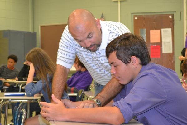 HARD AT WORK -- Mr. Plemons aids freshman Jake Biddy with an Algebra I assignment.