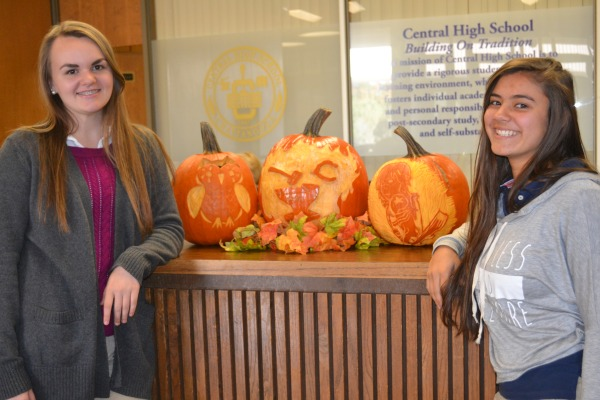PUMPKIN CARVING TRADITION -- Caitlin Maupin and Kelly Wnuk show off their detailed pumpkin carvings along with Mr. Rob's (center).
