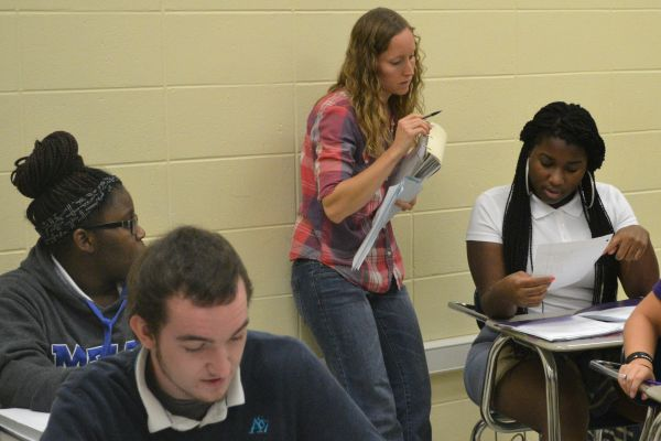 MRS. MIELKE GETS COMFORTABLE WITH CENTRAL MATH STUDENTS -- Mrs. Mielke works with students Brandon Jonhson (front left), Arteisha Cole (back left), and Ja Canna Boozer (right).