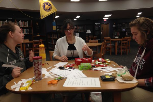 STUDENTS HONOR HARPER LEE WITH SILENT ACTS OF KINDNESS --- (left to right) Cheyenne Slaughter, Ms. Sally White, and Hannah Stone prepare the items they are handing out.