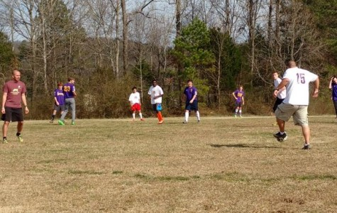 NEW SOCCER COACHES GET DOWN AND DIRTY SCRIMMAGING WITH THEIR TEAM -- Assistant Coach Jimmy Lessentine (left) and Head Coach Tim Browder (right) scrimmage with the boys to switch up the competition at practice.