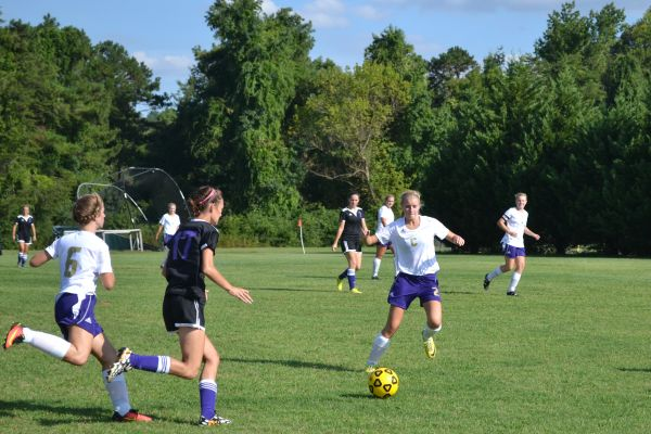LADY POUNDERS BRING HOME THEIR FIRST VICTORY-- Celisia Snakenberg (center) runs after the soccer ball to secure Central's possession.