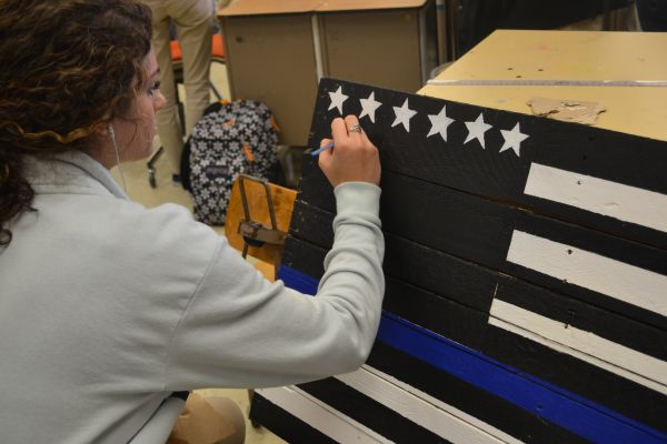 CENTRAL ART PROJECT COMMEMORATES FALLEN POLICE OFFICERS-- Gwendolyn Sofield, Central senior, shows respect for fallen police officers by painting project entitled