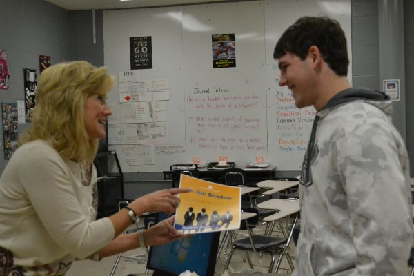 STEM TRIP FOR SENIORS -- Mrs. Holingsworth gives the job shadowing trip flier to  Johnathan Alston.