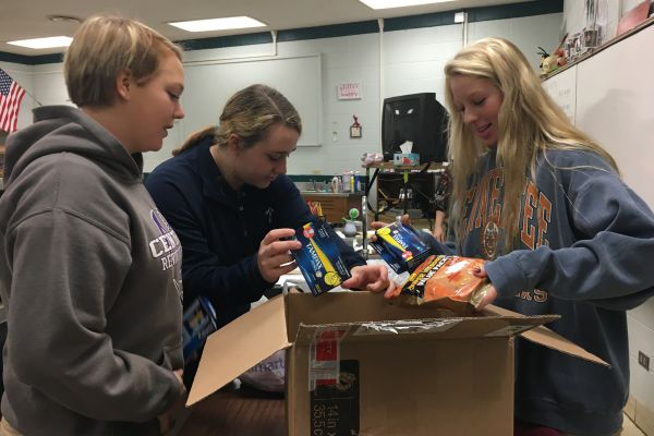 NATIONAL HONOR SOCIETY HELPS SOLDIERS -- Seniors Brooke Parrott, Lauren Reively, and Kymmy Stacks help pack treats for the soldiers.