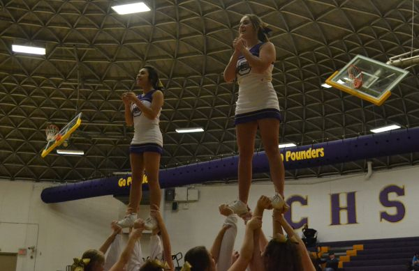 CHEERING ON THE POUNDERS -- Anahi Colunga (left) and Katee Herron (right) cheer on the purple pounders at a basketball game.