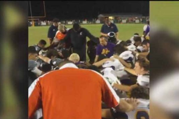 BUT SERIOUSLY:  WHEN CAN WE PRAY? -- Football players from Central and East Ridge players pray over an injured Central  athlete.