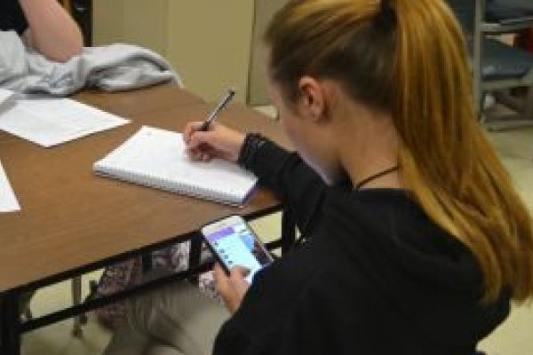 TEENS NEED A CELLULAR DETOX -- Student using phone while she should be working.