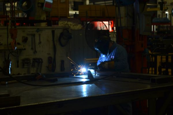 WELDER AT ROADTEC WORKING ON MACHINERY-- A Welder finishes parts during Central's trip to Roadtec