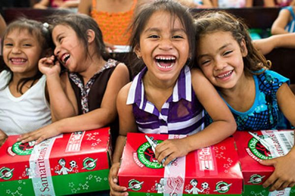 OPERATION CHRISTMAS CHILD GIVES GIFTS TO THOSE IN NEED-- Girls smile as they recieve their shoeboxes.