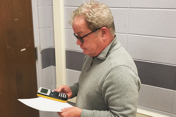 TEACHER SPOTLIGHT: JAMES SNYDER HELPS STUDENTS GET ON TRACK TO GRADUATE -- Mr. Snyder looks over a student's work.