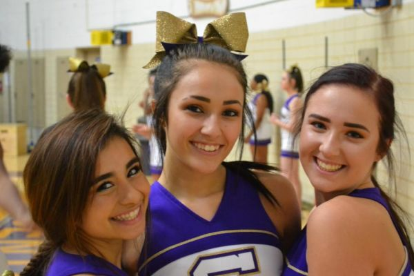 LET'S GO POUNDERS -- (left to right) Cheerleaders Anahi Colunga, Maggie Watts, and Meghan Duncan prepare for the match against the Pioneers.