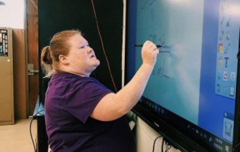 CHEMISTRY TEACHER MEGAN SANFORD MAKING A SPEEDY RECOVERY -- Mrs. Sanford is depicted working out a density problem on the Promethean board when she still taught at Central.