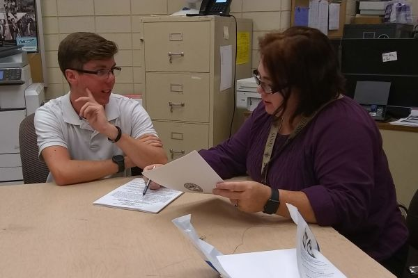 HOOPER ASSISTS STUDENT IN REVIEWING APPLICATION -- Mrs. Danielle Hooper (right) assists Junior, Grant Scutt (left), in reviewing application requirements for Governor's School.