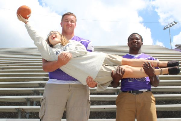 STUDENT SECTION OR SENIOR SECTION? -- Senior football players Wyatt Garret (left) and Michael Mcghee (right) hold Columnist Laurelie Holmberg up to catch a ball.