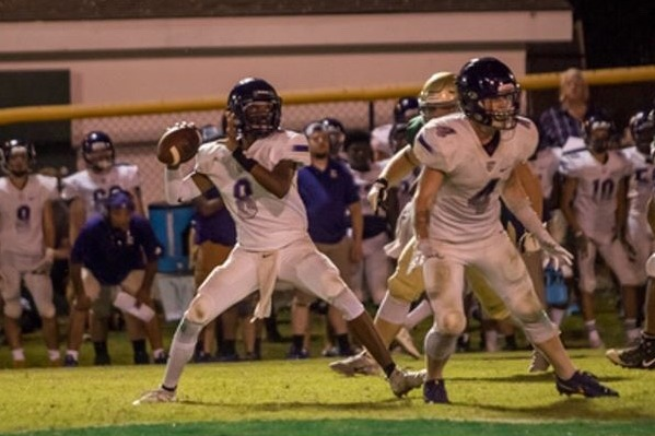 FRIDAY NIGHT LIGHTS HAVE FINALLY ARRIVED --- Senior Kelvin McGhee, throwing the ball while senior, Hunter Jones protects him in the backfield.