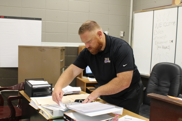 RYAN MALLORY VOLUNTEERS TO BECOME SPONSOR OF THE BETA CLUB -- Mr. Ryan Mallory is pictured organizing his heavy workload while working as the new Beta Club sponsor.