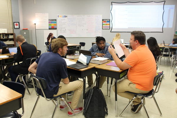 SENIOR CLASS OF 2020  STRIVES TO RAISE GRADUATION RATE -- Senior English teacher Adam Fletcher helps his students get their work done.