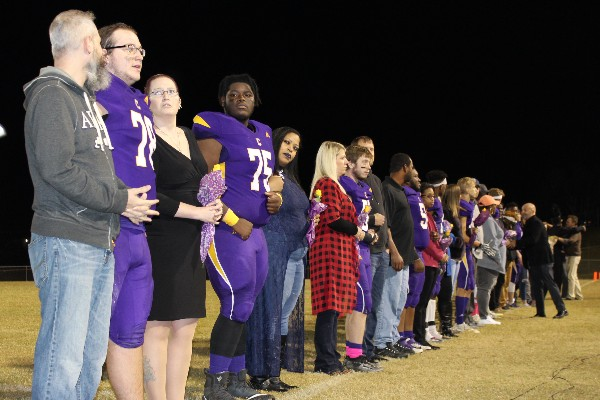 FOOTBALL SENIOR NIGHT 2019 -- The Senior Class of 2020 football players and band performers stand before the audience to be recognized. Each student is accompanied by friends and family.