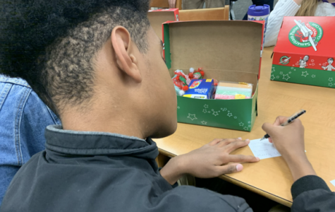 FCA SUPPORTS OPERATION CHRISTMAS CHILD BY COLLECTING GIFT DONATIONS — A student packs a gift box for Operation Christmas Child to spread holiday cheer to less fortunate children.