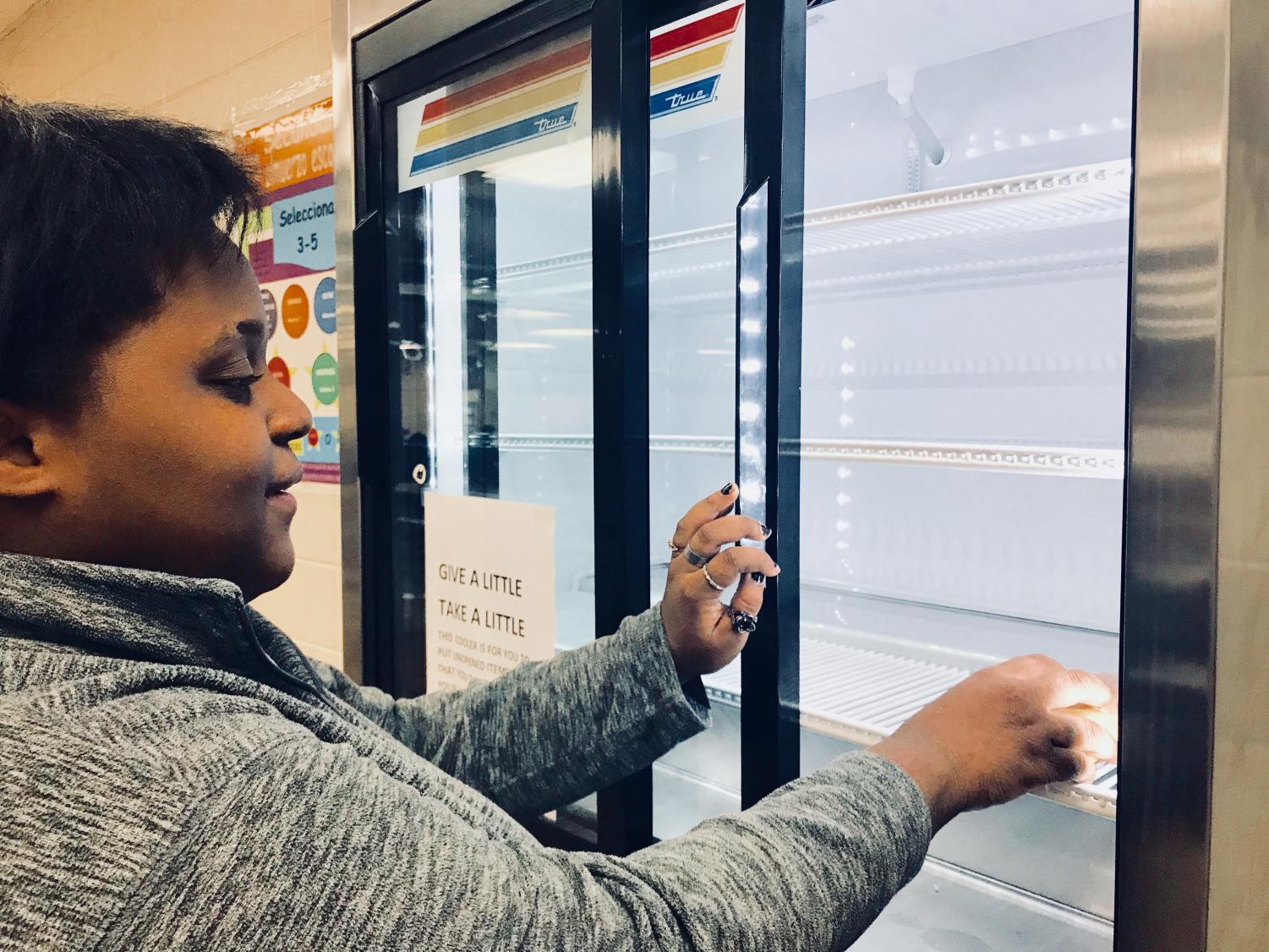 LUNCH LADIES PUT A POSSIBLE STOP TO FOOD WASTE WITH A FREE FOOD PANTRY — Ashauna Parrish places an unopened food item in the designated cooler for another student to enjoy.