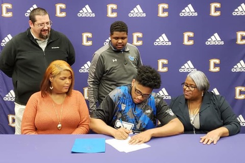 CEDRIC WILLIAMS IS AWARDED SEVERAL SCHOLARSHIP FOR EXCELLENCE IN BOWLING -- Cedric Williams signs alongside his family members and Coach Potter.