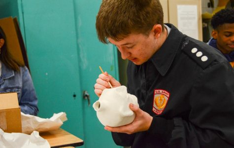 ART CLASSES CELEBRATE BLACK HISTORY MONTH WITH FACE JUGS -- Art student Hyatt Green paints a replica face jug.