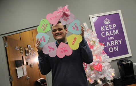 EDITORIAL: LOVE IS IN THE AIR AT CENTRAL HIGH -- Senior James Ortiz, viewed as the most lovable person at Central High, poses with Valentine's Day decorations.
