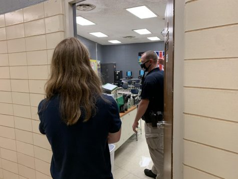COVID-19 CAUSES LITTLE CHANGE UP IN INTRUDER DRILL -- Officer Marcus Dotson explains intruder drill procedures to a student.