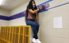2020 LEADERSHIP CLASS TOUCHES UP THE WALLS OF CENTRAL-- Senior Dallana Nolazco sits on a locker while touching up the walls of the basketball locker rooms.