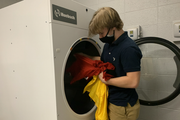 THE SPORTS DEPARTMENT'S NEW DRYER -- Senior Roby Thomas puts practice gear in the dryer to dry.