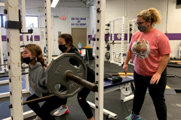 CENTRAL WELCOMES COACHES SHURETTE AND WARE TO SOFTBALL -- Juniors Ashlyn Wood and Calli Morgan work hard in the weight room as Coach Shurette looks on and encourages.