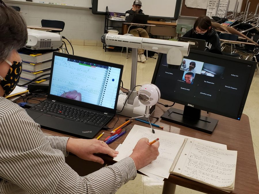 COVID-19 PANDEMIC CAUSES A DROP IN MATH COMPREHENSION -- Peggy Moyer is teaching her students on campus and through Zoom. She uses her Elmo to project what she writes to both groups of students.