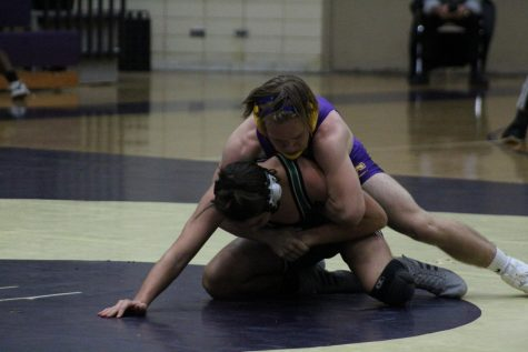 A WRESTLING UPDATE -- Senior Roby Thomas attempts to pin his opponent to the ground.