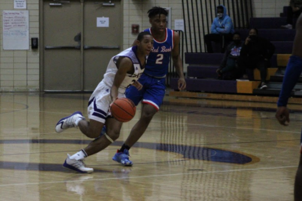BOYS' BASKETBALL PHOTO GALLERY -- Donovin Taylor runs past his opponent and towards the net.