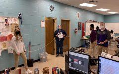 FEBRUARY'S TEACHER OF THE MONTH -- Sophomore Amber Burchfield and Junior Luke Keown six feet apart (measured) from February's Teacher of the Month, Nathan Dawson.