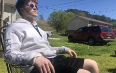 SPRING...BREAK? STAY? -- Grayson Catlett sits and enjoys the sun at home (not a crowded Florida beach).