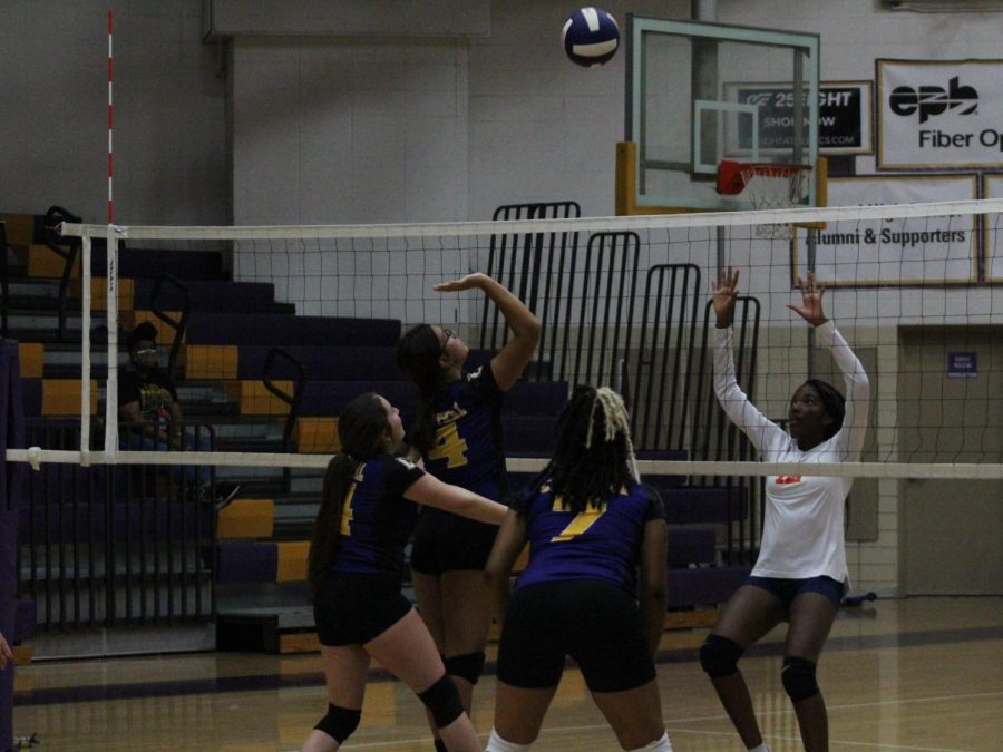 The lady pounders spike the ball down, earning a point, against East Ridge High School.