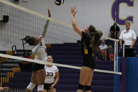 Addason Wellington spiking the ball down, earning a point for the lady pounders.